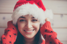 head shot of a woman in a Santa hat and Christmas sweater