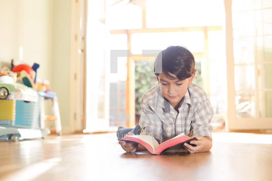 boy reading bible lying on floor