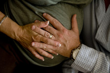 mother and father's hands on a pregnant belly