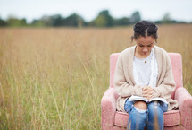 a woman sitting in a chair with praying hands over a Bible in a field
