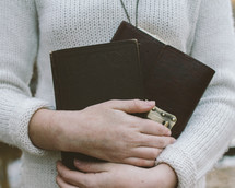 woman holding a Bible and journal close to her heart