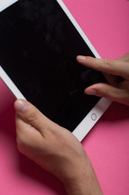 Hands holding an electronic tablet on a pink background.