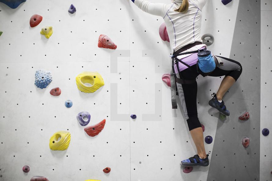 woman climbing an indoor rock wall.