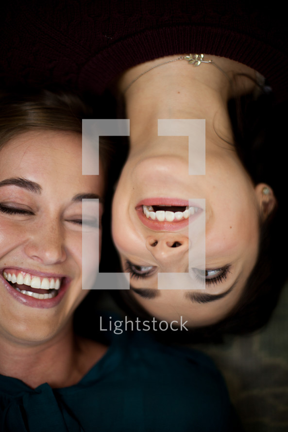 smiling friends lying on a floor