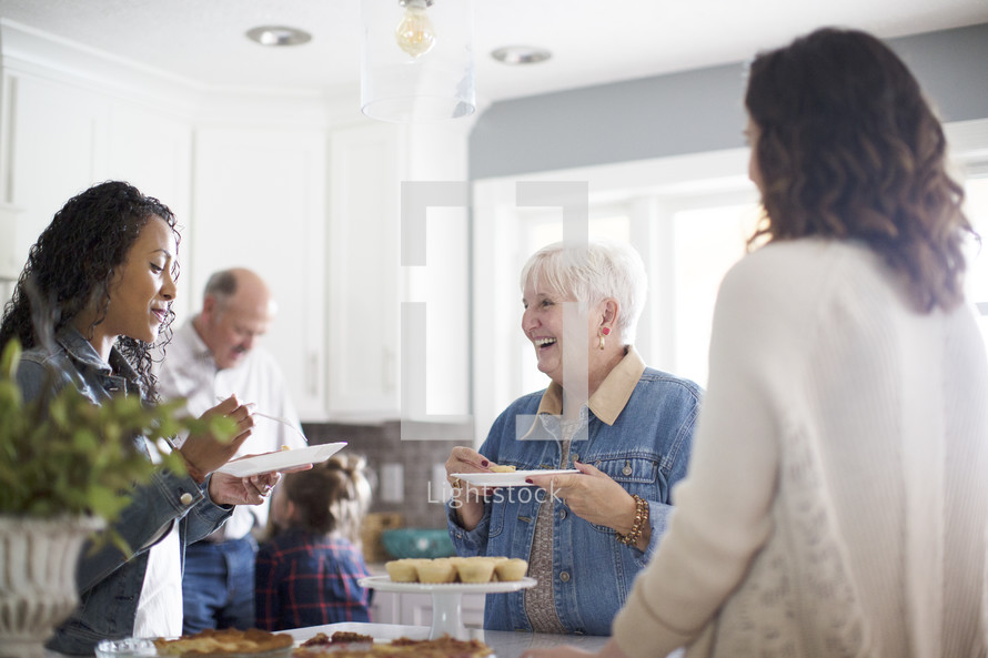 family gathered in the kitchen to get dessert at Thanksgiving