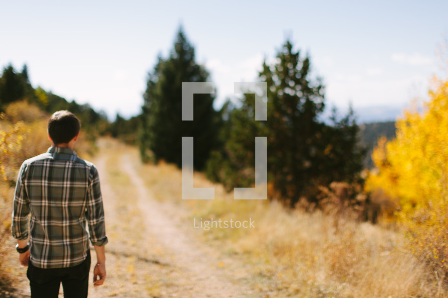 a man walking down a dirt road carrying a Bible