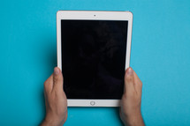 Hands holding an electronic tablet on a blue background.