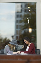 young women praying together at an outdoor table.