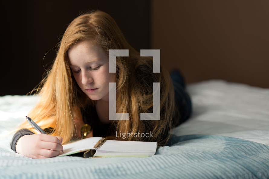 teen girl writing in a journal lying on a bed