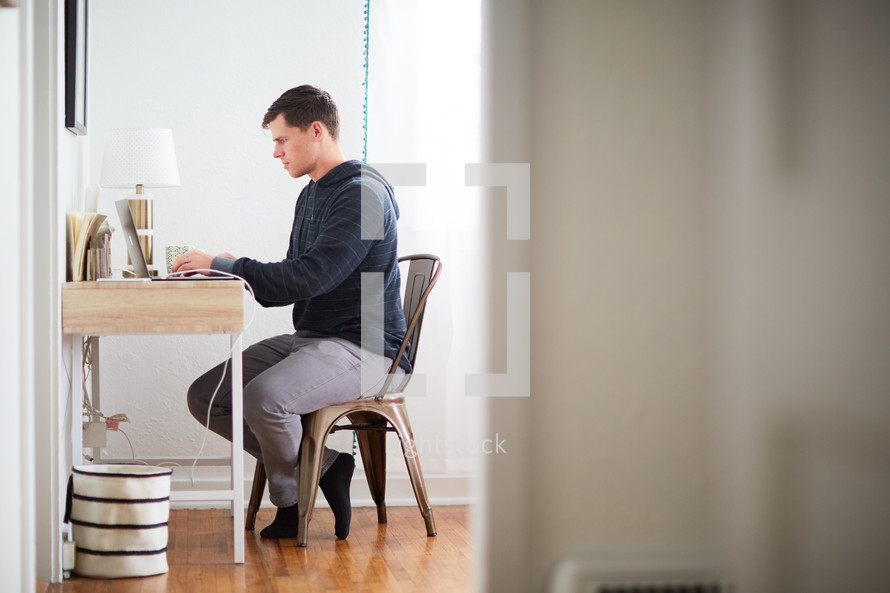 a man sitting in front of a computer at a desk