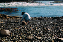 a person looking for seashells