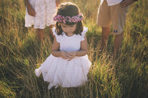 a toddler girl picking grass at sunset