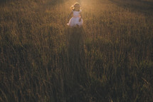 a girl child in a dress running through tall grass at sunset
