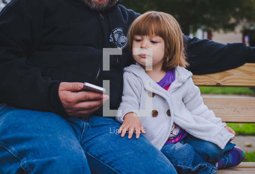 father and daughter looking at a cellphone screen
