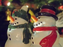 Two snowmen figures enjoy the Christmas festivity of lights, color, sounds and smells of Christmas that bring a smile to all who experience it as these two figures revel in the joy that is Christmas.