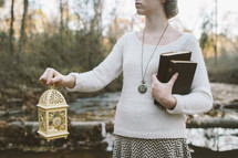 woman carrying a lantern and Bible and journal