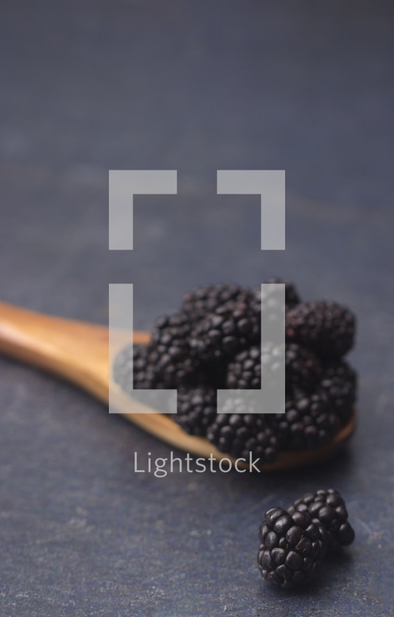 wooden spoon full of blackberries