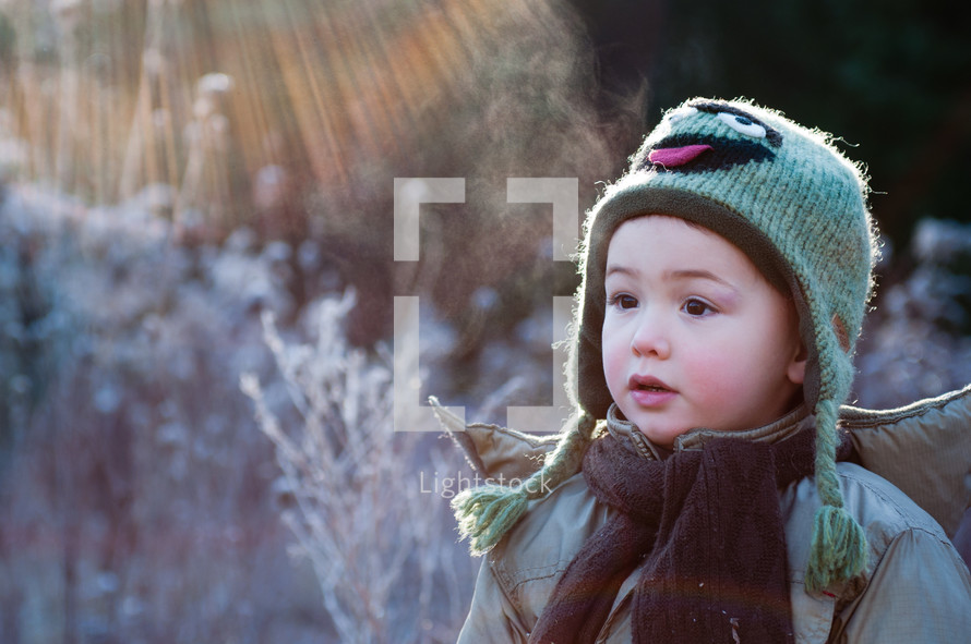 toddler boy standing outdoors in winter