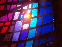 Colorful stained glass windows with shades of blue, red and  purple let the sunlight pour into a church prayer chapel