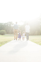family walking outdoors holding hands together.