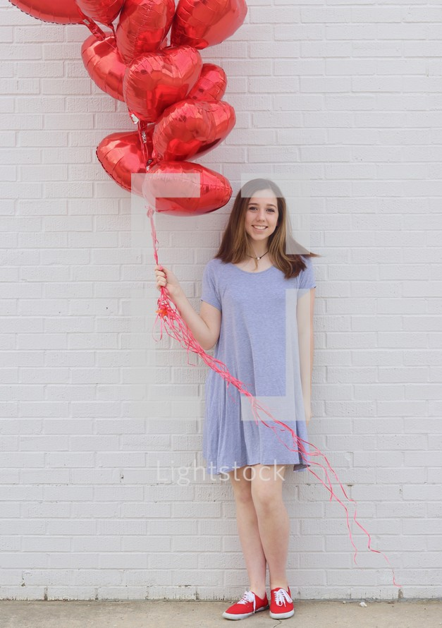 teen girl holding red heart shaped helium balloons