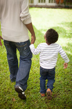 father and son walking holding hands outdoors