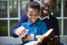 Father and son happily reading the Bible together.