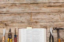 Tools and a Bible lined up on a rustic wooden table.