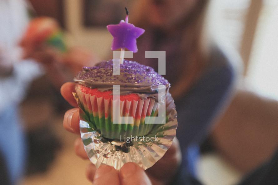 A girl holding a birthday cupcake