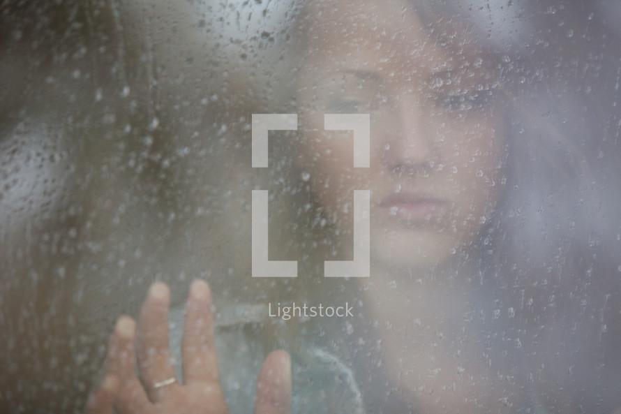 Teenage girl looking out a rainy window pane.