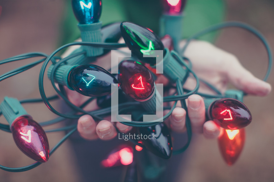 A woman holding a tangle of multi-colored Christmas lights.