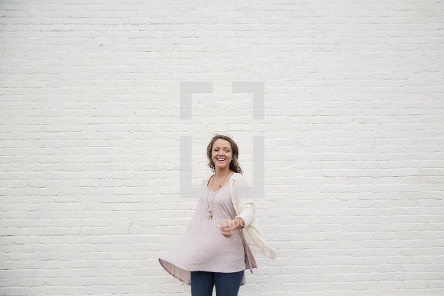A woman standing in front of a white wall dancing.