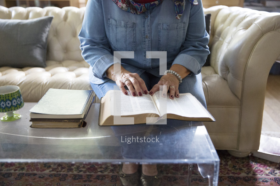 an elderly woman reading a Bible in a living room