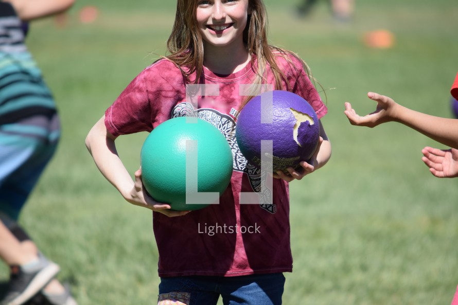a little girl holding dodge balls