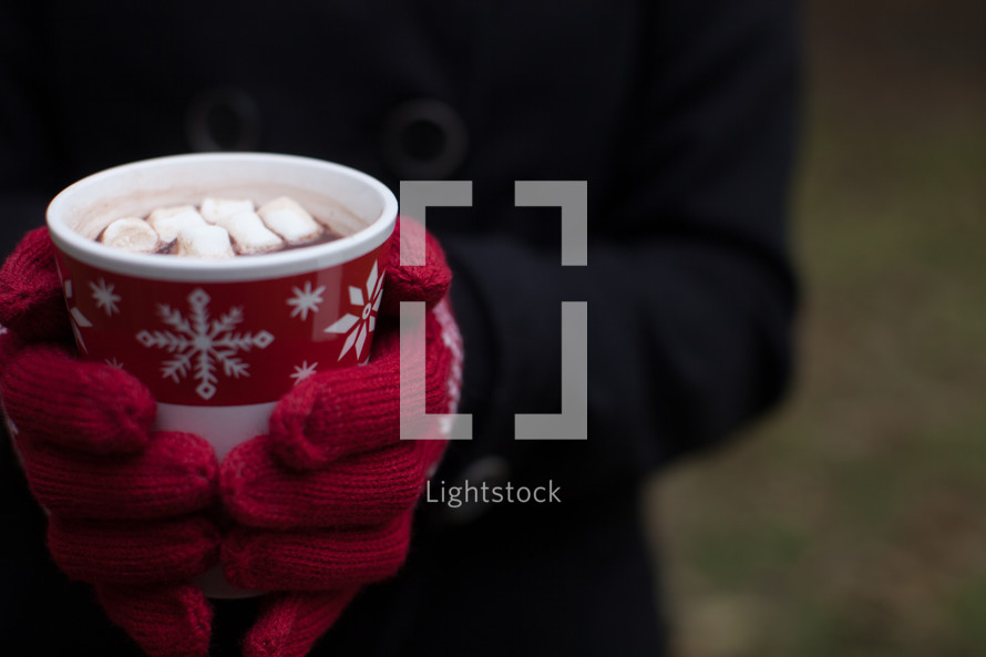 A Christmas cup of hot chocolate with marshmallows being held by a woman wearing red mittens.