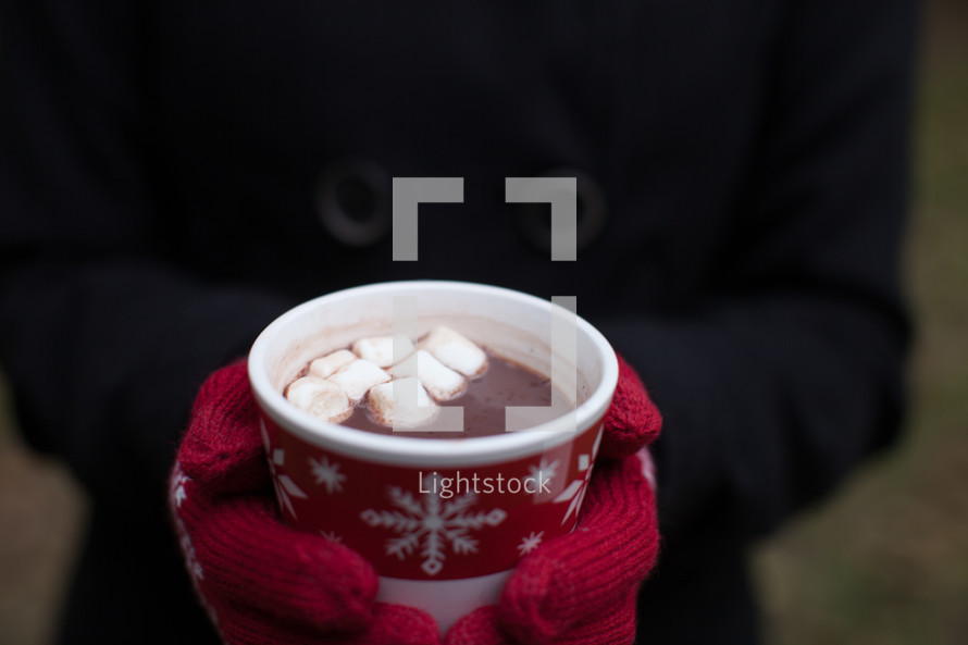 A Christmas cup of hot chocolate being held by a woman wearing red mittens.