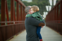 father and son hugging outdoors
