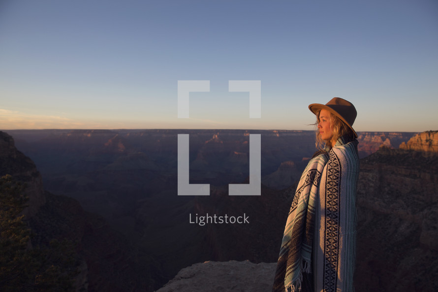 a woman wrapped in a blanket at the top of a canyon at sunset