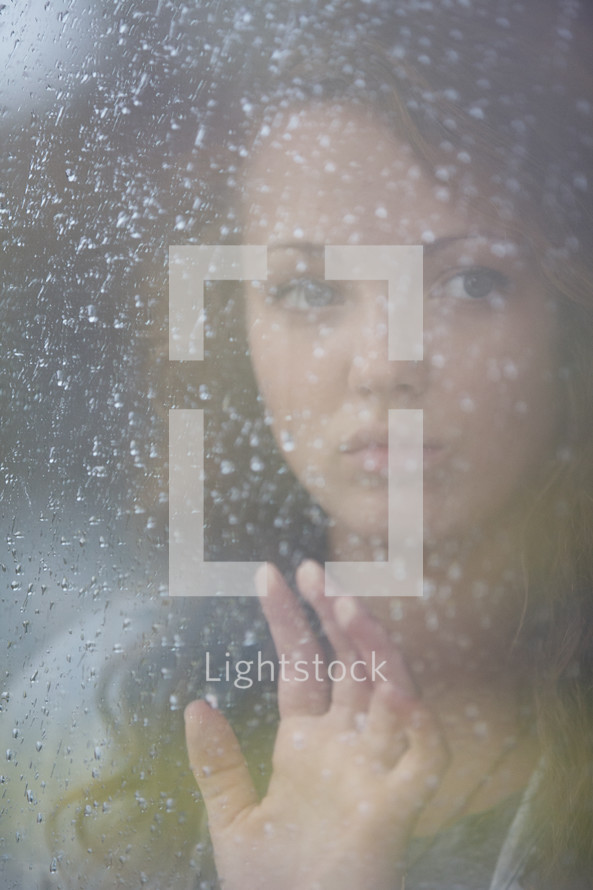 Woman looking out a frosted window.