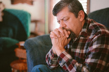a man sitting on a couch praying
