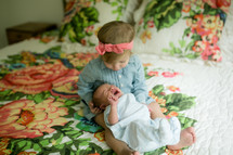 big sister holding her newborn brother