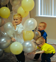 toddlers playing with helium balloons