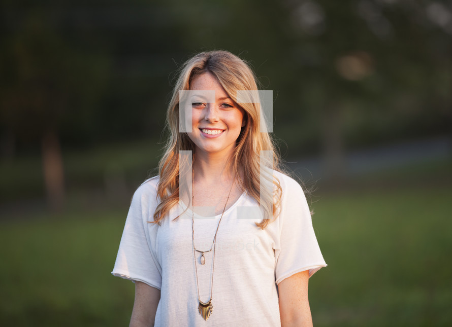 a portrait of a smiling young woman outdoors