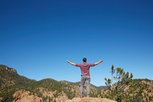 a man standing with open arms with mountain view
