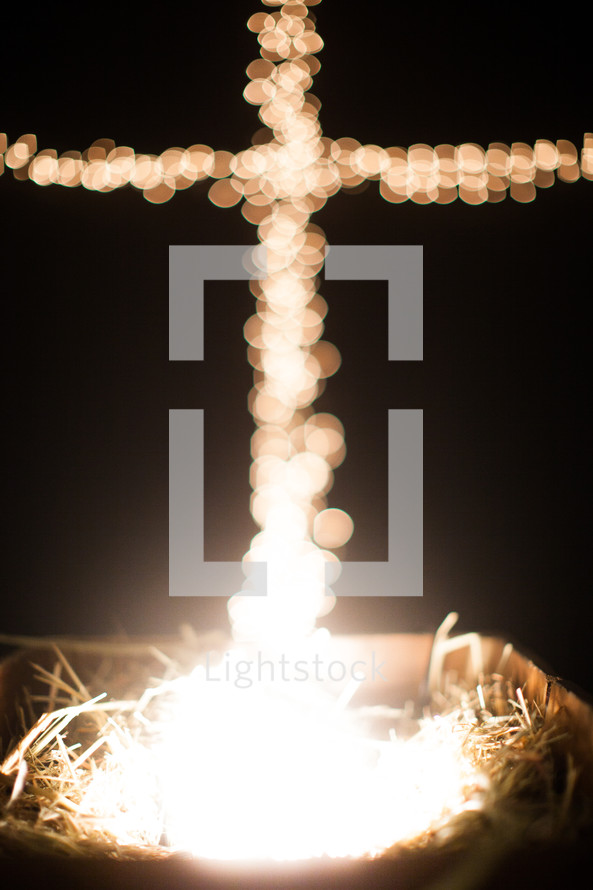 bokeh Christmas lights in the shape of a cross and a manger