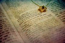 Open Hebrew - English Bible with golden Star of David pendant on the page.