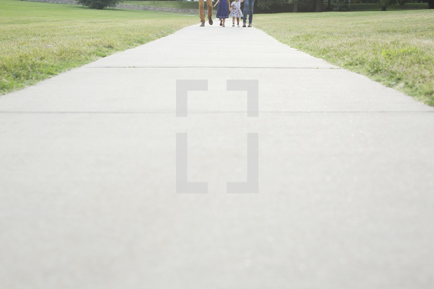 distant family walking outdoors holding hands