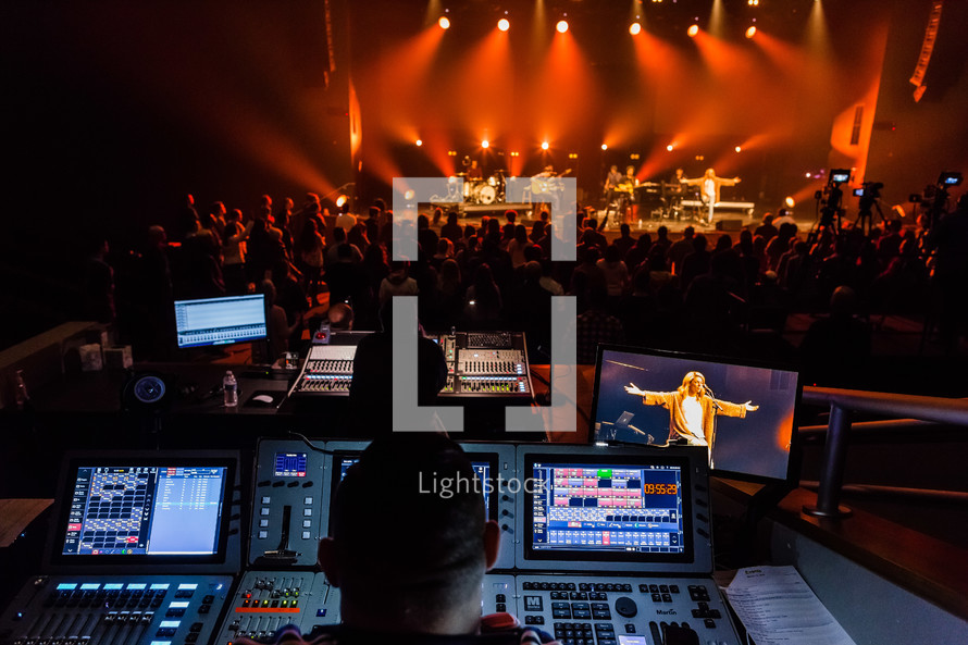 production crews controlling lights and sound at a concert