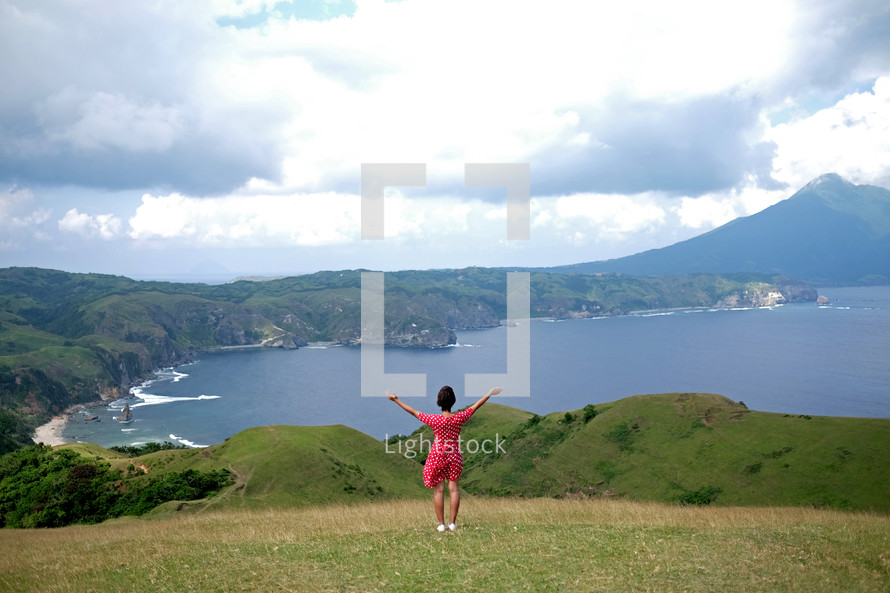 A woman in a pink dress stands on a green hill with arms outstretched toward the ocean.