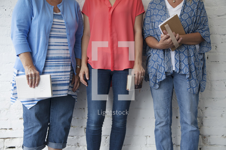 torsos women holding Bibles standing in front of a white wall